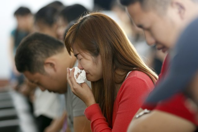 Relatives of the crashed AirAsia plane passengers pray at Juanda Airport, in Surabaya, Indonesia, 31 December 2014. Indonesian rescuers retrieved three more bodies from the sea on 31 December but the search to recover more victims from the AirAsia plane crash was hampered by bad weather, the recue chief said. (Photo by Made Nagi/EPA)