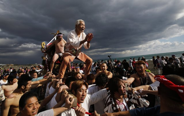 "Men ride on a ""mikoshi"" or portable shrine as local people carry it into the sea during a festival to wish peace in the ocean and good fortune in the new year in Oiso, west of Tokyo, January 1, 2015. (Photo by Yuya Shino/Reuters)"