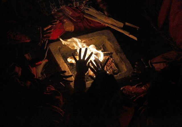 The hand of a devotee is silhouetted as she sits beside a fire to keep warm before taking a holy bath in Saali River on the first day of the Swasthani Brata Katha festival at Sankhu in Kathmandu January 5, 2015. (Photo by Navesh Chitrakar/Reuters)