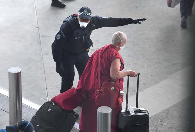 A police officer directs a returning passenger after arriving on a special Nepal Air flight repatriating Australian and New Zealanders from overseas, in Brisbane airport, Thursday, April 2, 2020. The chartered flight out of Nepal had 222 Australians and 28 New Zealand citizens and permanent residents onboard. (Photo by Dan Peled/AAP Image)
