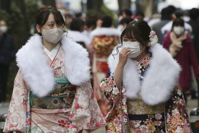 Kimono-clad women wearing face masks to protect against the spread of the coronavirus walk together following a Coming-of-Age ceremony in Yokohama, near Tokyo, Monday, January 11, 2021. The Tokyo area has been under a state of emergency since Friday to try to stop the spread of the virus. (Photo by Koji Sasahara/AP Photo)