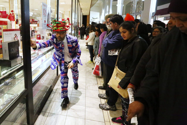 A crowd is held back as Macy's store manager Reza Baharmast, at left, slides the doors open as the store opens at 6 p.m. on Thanksgiving Day at Westfield Southcenter mall Thurs., November 26, 2015, in Tukwila. (Photo by Ken Lambert/The Seattle Times)