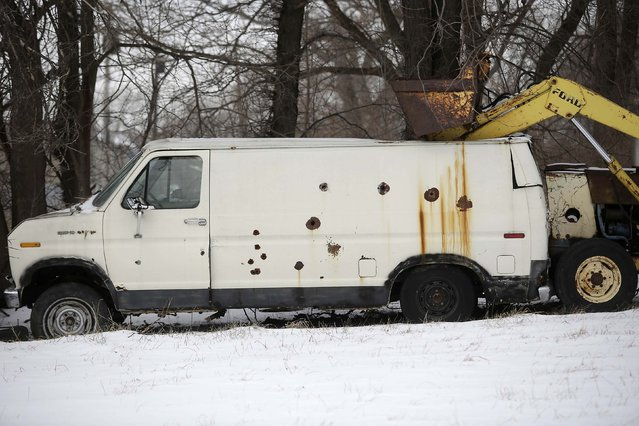 An older Ford van with holes and rust spots sits in the yard next to a tractor in Detroit, Michigan January 10, 2015. (Photo by Joshua Lott/Reuters)