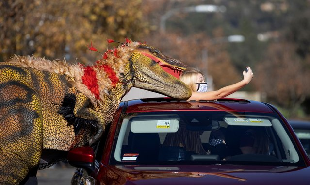 Samantha Bailey takes a selfie with a staff member dressed like a raptor at the Jurassic Quest drive-thru Experience outside The Rose Bowl Stadium during the outbreak of the coronavirus disease (COVID-19), in Pasadena, California, U.S., January 15, 2021. (Photo by Mario Anzuoni/Reuters)