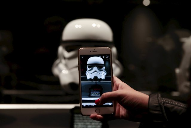 A guest takes a photo of a replica stormtrooper helmet during the Star Wars Launch Bay grand opening at Disney's Hollywood Studios in Orlando, Florida December 4, 2015. (Photo by Scott Audette/Reuters)