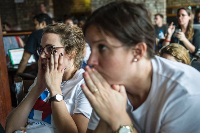 A crowd of American supporters of US presidential candidate Democrat Hillary Clinton reacts while watching a live broadcast of the US presidential election at a restaurant in Yangon on November 9, 2016. Donald Trump has stunned America and the world, riding a wave of populist resentment to defeat Hillary Clinton in the race to become the 45th president of the United States. (Photo by Romeo Gacad/AFP Photo)