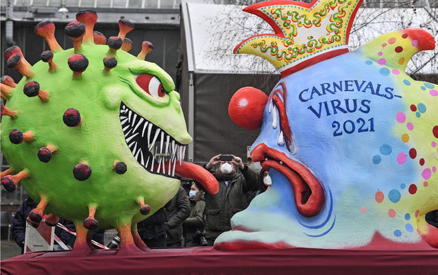 A political carnival float depicting the coronavirus vs the carnival virus is rolled out to be shown in the streets when the traditional carnival parade was canceled due to the coronavirus pandemic in Duesseldorf, Germany,  Monday, February 15, 2021. (Photo by Martin Meissner/AP Photo)