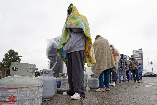 Carlos Mandez waits in line to fill his propane tanks Wednesday, February 17, 2021, in Houston. Customers had to wait over an hour in the freezing rain to fill their tanks. Millions in Texas still had no power after a historic snowfall and single-digit temperatures created a surge of demand for electricity to warm up homes unaccustomed to such extreme lows, buckling the state's power grid and causing widespread blackouts. (Photo by David J. Phillip/AP Photo)