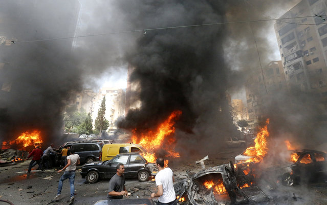 Civilians gather at the of an explosion in Beirut's southern suburb neighbourhood of Bir al-Abed on July 9, 2013.  A car bomb rocked Beirut's southern suburbs, stronghold of Lebanon's Shiite Hezbollah movement,  wounding 15 people, television reports and a military source said. (Photo by AFP Photo/STR)