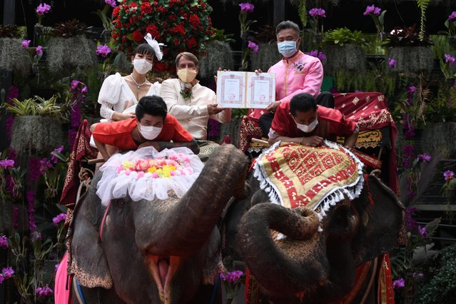 A couple receives marriage certificates from a provincial officer as they ride elephants during a Valentine's Day celebration at the Nong Nooch Tropical Garden in Chonburi province, Thailand, February 14, 2021. (Photo by Chalinee Thirasupa/Reuters)