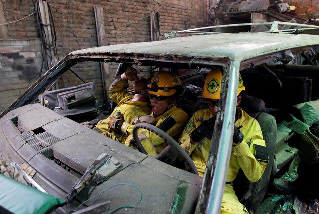 Comandos de Salvamento rescuers Emmanuel Martinez (L), Brandon Martinez (C), and Joel Altamirano rest during a car accident rescue practice in San Salvador, El Salvador July 27, 2016. (Photo by Jose Cabezas/Reuters)