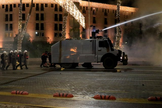 A police water cannon operates against protesters during clashes in Tirana, Friday, December 11, 2020. Albanian demonstrators clashed in the third day on Friday protesting for the death of a 25-year-old man shot dead by a police officer. (Photo by Hektor Pustina/AP Photo)