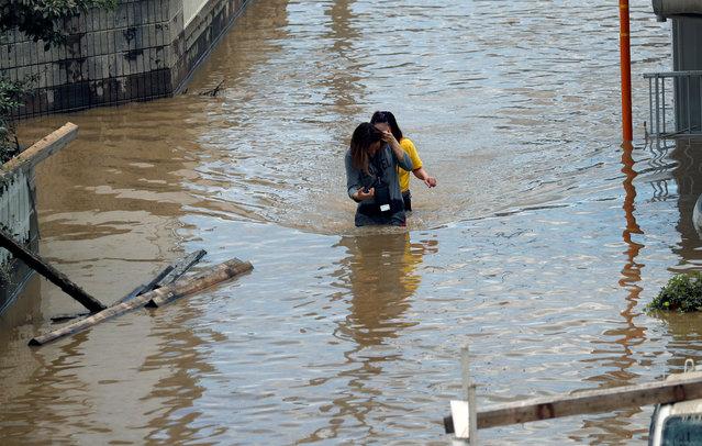 Women make their way through a flooded area in Mabi town in Kurashiki, Okayama Prefecture, July 8, 2018. (Photo by Issei Kato/Reuters)