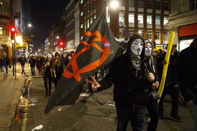 """Masked protesters taking part at the 'Million Mask March' demonstration organised by activists Anonymous in London, England on November 5, 2014. The event has become associated with protesters donning the Guy Fawkes mask made famous by graphic novel and film of """"V for Vendetta"""" and now used around the world as a symbol of anarchy. (Photo by Tolga Akmen/Anadolu Agency/Getty Images)"""