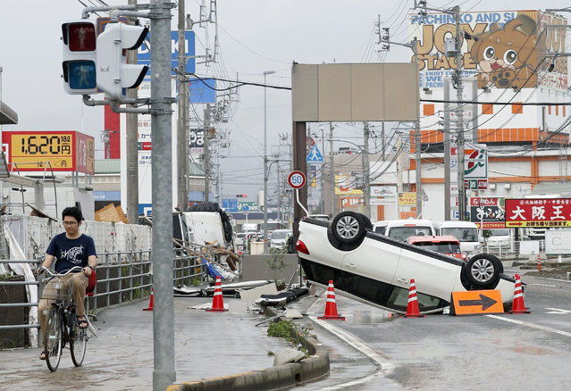 An overturned car is seen on a road following heavy rain in Ozu city, Ehime prefecture, southwestern Japan, Sunday, July 8, 2018. Heavy rainfall hammered southern Japan for the third day, prompting new disaster warnings on Kyushu and Shikoku islands on Sunday. (Photo by Michi Ono/Kyodo News via AP Photo)