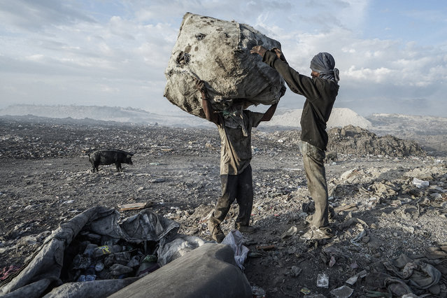 In a 200-acre-plus dump 5 kilometers north of Haiti's capital, Port-au-Prince, hundreds of men, women and children scavenge day and night through the burning wasteland. They earn $12 to $15 a day – on a good day – for recycling plastics as well as clothing, household items and aluminum (for smelting). Some 5,000 tons of waste is created each day in the Port-au-Prince area. (Photo and caption by Giles Clarke/Getty Images Reportage)