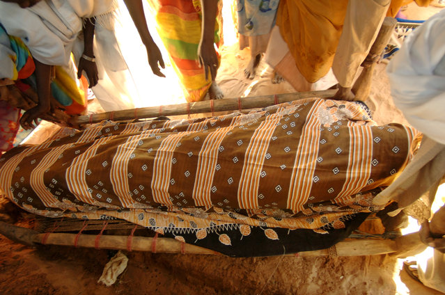 Villagers wrap the body of an old woman before her burial in the Kalma camp for internally displaced people in Nyala, south Darfur, Sudan, on November 6, 2005. As fighting continued across Darfur between Arab nomads backed by government forces and ethnic Africans, hundreds of thousands of internally displaced civilians flooded the camps. (Photo by Lynsey Addario)