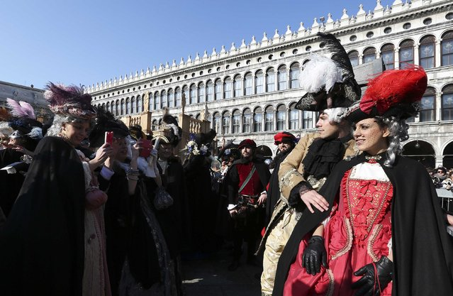Masked revellers have their picture taken in Saint Mark Square during carnival in Venice February 8, 2015. (Photo by Stefano Rellandini/Reuters)
