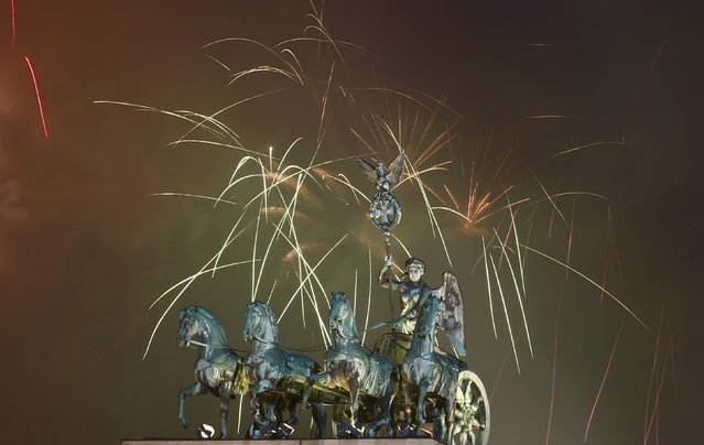 Fireworks explode next to the Quadriga sculpture atop the Brandenburg gate during New Year celebrations in Berlin January 1, 2016. (Photo by Hannibal Hanschke/Reuters)