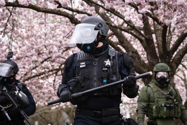 """An Oregon State Police officer wears riot gear and holds a baton after an official declaration of an """"unlawful assembly"""" during an anti-fascist rally in Salem, Oregon, U.S., March 28, 2021. (Photo by Maranie R. Staab/Reuters)"""