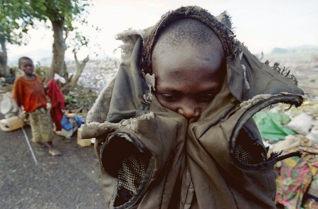 A young Rwandan refugee who travelled from Bukavu with several thousand others shivers in the early morning in this November 30, 1996 file photo before getting back on the road to the border. He was part of a group of some 20,000 refugees, many suffering from disease and malnutrition, who had made their way into Goma after being on the road for over one month. (Photo by Corinne Dufka/Reuters)
