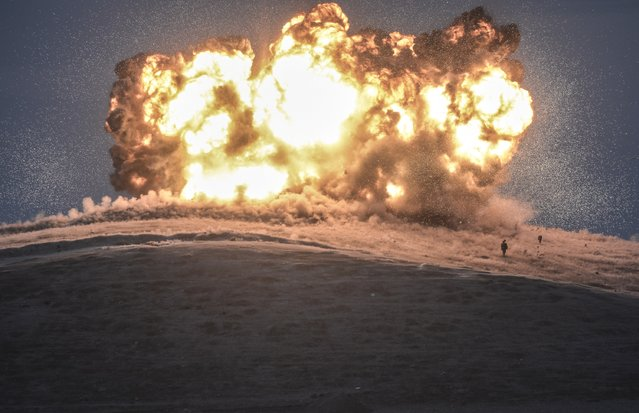 A file photo taken on October 23, 2014 shows militants of Islamic State (IS) standing just before explosion of an air strike on Tilsehir hill near Turkish border, at Yumurtalik village,  in Sanliurfa province. Bulent Kilic was awarded with the World Press Spot News Single third prize for this photo on February 12, 2015. (Photo by Bulent Kilic/AFP Photo)