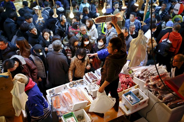 Fishmongers offer their goods for sale as people crowd Ameyoko market to shop for food and goods ahead of the New Year holidays in Tokyo, Japan, December 30, 2015. (Photo by Thomas Peter/Reuters)