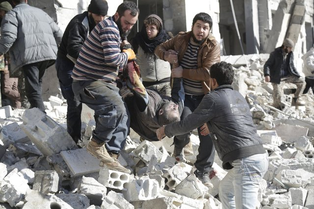 Residents carry an injured man in a site hit by what activists said were airstrikes carried out by the Russian air force in the rebel-controlled area of Maaret al-Numan town in Idlib province, Syria January 9, 2016. (Photo by Khalil Ashawi/Reuters)