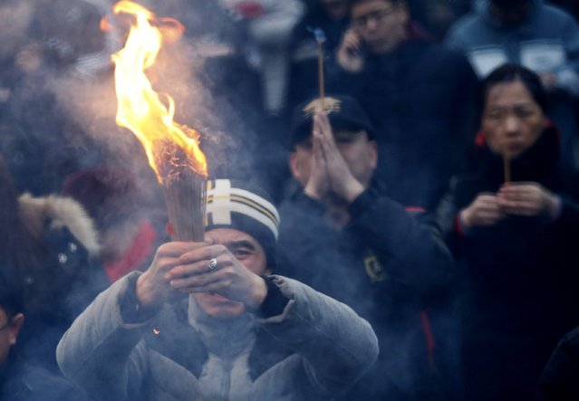 People pray for good fortune as they hold burning incenses on the first day of the Chinese Lunar New Year at Yonghegong Lama Temple, in Beijing, February 19, 2015. (Photo by Kim Kyung-Hoon/Reuters)