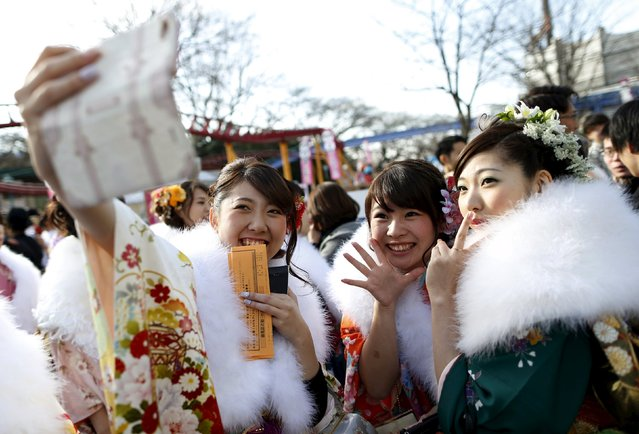 Japanese women wearing kimonos take pictures during their Coming of Age Day celebration ceremony at an amusement park in Tokyo January 11, 2016. According to a government announcement, more than 1.2 million men and women who were born in 1995 marked the coming of age this year, a decrease of approximately 50,000 from last year. (Photo by Yuya Shino/Reuters)