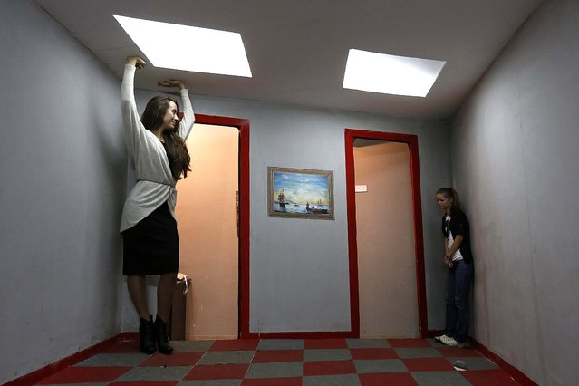 Visitors look at each other in an Ames room at a private exhibition of optical Illusions in St. Petersburg, Russia, on September 24, 2013. An Ames room is constructed with a distorted perspective to confuse observers' sense of scale. (Photo by Alexander Demianchuk/Reuters)