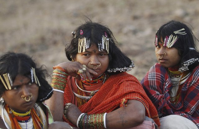 In this Saturday, February 21, 2015 photo, members of India's Dongria tribe watch their traditional dance being performed by others during the two-day long Niyamraja Festival atop the Niyamgiri hills near Lanjigarh in Kalahandi district, Orissa state, India. (Photo by Biswaranjan Rout/AP Photo)