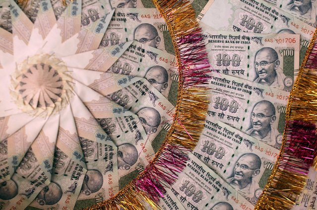 A garland made of Indian currency notes is pictured in a shop at a market in Jammu, India, November 13, 2016. (Photo by Mukesh Gupta/Reuters)