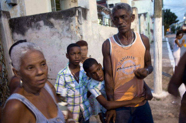 In this September 27, 2013 photo, Adrian Cueto, 11, center, embraces his father Ramon as his twin brother Arian looks on during interviews in Havana, Cuba. The Cueto brothers are just one set of twins out of 12 sets living along two consecutive blocks in western Havana. (Photo by Ramon Espinosa/AP Photo)