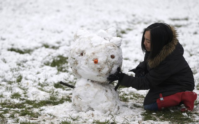 A woman builds a snow kitten in north London, Britain January 17, 2016. (Photo by Neil Hall/Reuters)