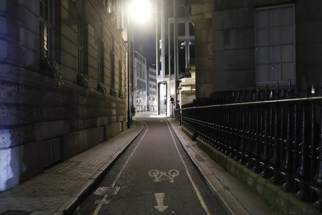 """A view of an empty Gutter Lane in the City of London on Saturday, March 6, 2021. When the pandemic struck, about 540,000 workers vanished from London's financial hub almost overnight. The area known as """"the City"""" became a ghost town as many people began working from home. A year on, most haven't returned to the business hub. While many people believe that post-pandemic workflow will become the new normal, skyscrapers are still rising, and city planners say they aren't worried about empty office blocks. (Photo by Alastair Grant/AP Photo)"""