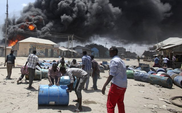 People move oil barrels away from the site of an explosion at a petrol station and storage facility near the Bakara open-air market in Somalia's capital Mogadishu, February 23, 2015. (Photo by Ismail Taxta/Reuters)