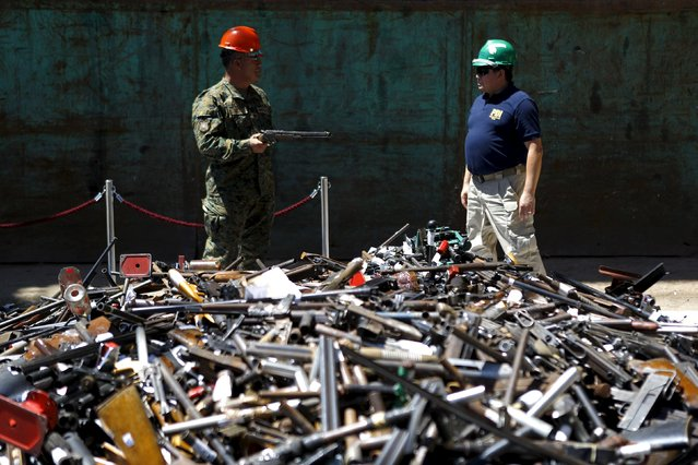 An army member inspects a weapon as he talks to a policeman in front of a pile of confiscated weapons before being destroyed at a foundry in Santiago, Chile, January 18, 2016. (Photo by Ivan Alvarado/Reuters)