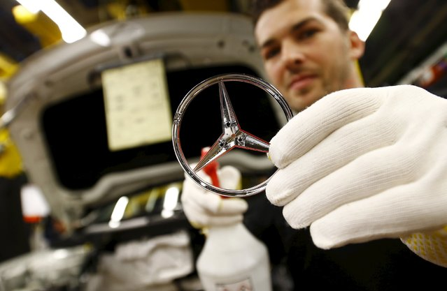 An employee of German car manufacturer Mercedes Benz cleans the brand's characteristic star before assembling it to a GLA model at their production line at the factory in Rastatt, Germany, January 22, 2016. (Photo by Kai Pfaffenbach/Reuters)