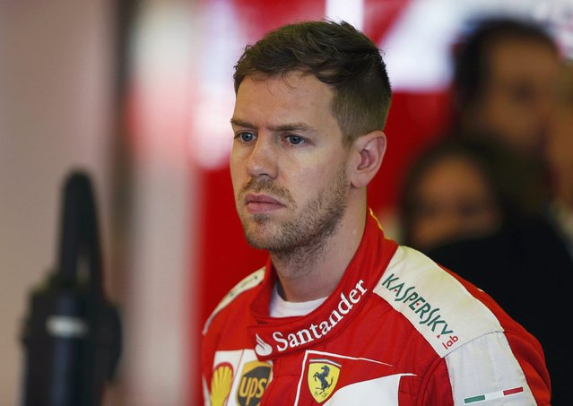 Ferrari Formula One driver Sebastian Vettel of Germany looks on in the team garage during the first practice session of the Australian F1 Grand Prix at the Albert Park circuit in Melbourne March 13, 2015. REUTERS/Brandon Malone