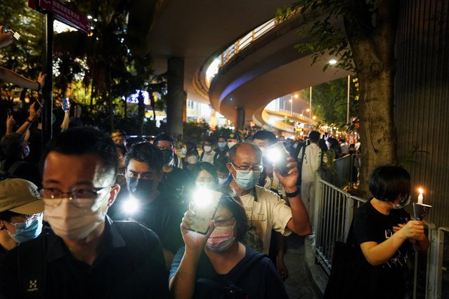 People flash lights from their mobile phones, as they walk on the road outside Victoria Park after police officers dispersed them on the 32nd anniversary of the crackdown on pro-democracy demonstrators at Beijing's Tiananmen Square in 1989, in Hong Kong, China on June 4, 2021. (Photo by Lam Yik/Reuters)