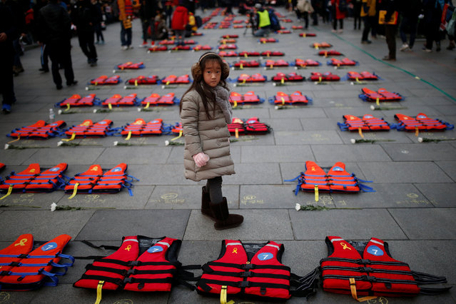 A girl stands between life vests symbolising the 304 victims of sunken ferry Sewol during a protest demanding South Korean President Park Geun-hye's resignation in Seoul, South Korea December 17, 2016. (Photo by Kim Hong-Ji/Reuters)
