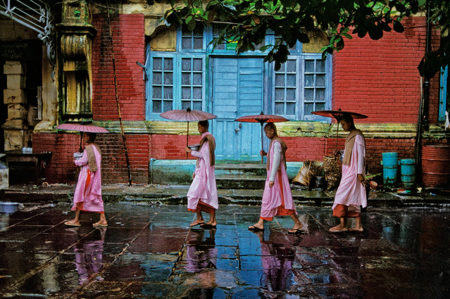 """Procession of nuns. Yangon, Myanmar, 1994, by Steve McCurry. """"I asked a group of Buddhist nuns if I could follow them as they carried their alms bowls during their rounds through the streets of Yangon, Myanmar. They gather alms and food from local people, who donate in order to demonstrate their humility and connection with their Buddhist faith"""". (Photo by Steve McCurry/Magnum Photos)"""