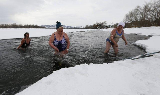 Zinaida Bulygina (C), 65, Ludmila Timofeeva (L), 53, and Anna Ushayeva, 65, members of a winter swimmers family club, swim in the icy waters of the Tuba river in the Kuragino village, southeast of the Russian Siberian city of Krasnoyarsk, March 17, 2015. (Photo by Ilya Naymushin/Reuters)