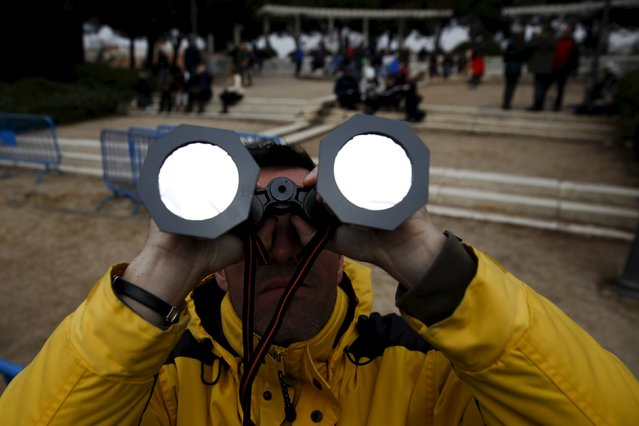 A man uses binoculars with special filters as he watches a partial solar eclipse, despite the cloudy weather, at Madrid's Planetarium March 20, 2015. A solar eclipse swept across the Atlantic Ocean on Friday with the moon set to block out the sun for a few thousand sky gazers on remote islands with millions more in Europe, Africa and Asia getting a partial celestial show. (Photo by Sergio Perez/Reuters)