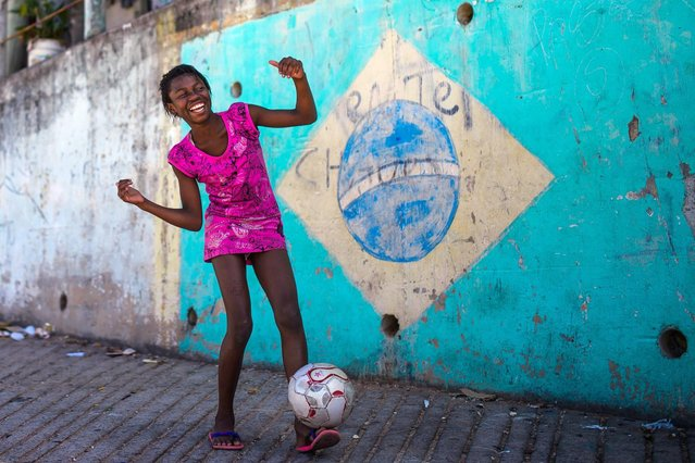A girl poses while playing football in the Chacara do Ceu favela, or shantytown, on November 3, 2013 in Rio de Janeiro, Brazil. The favela was previously controlled by drug traffickers and is now occupied by the city's Police Pacification Unit (UPP). Football is a very popular pastime played throughout the shantytowns of Rio and all over Brazil. The UPP are patrolling Rio's favelas amid the city's efforts to improve security ahead of the 2014 FIFA World Cup and 2016 Olympic Games. (Photo by Buda Mendes/Getty Images)