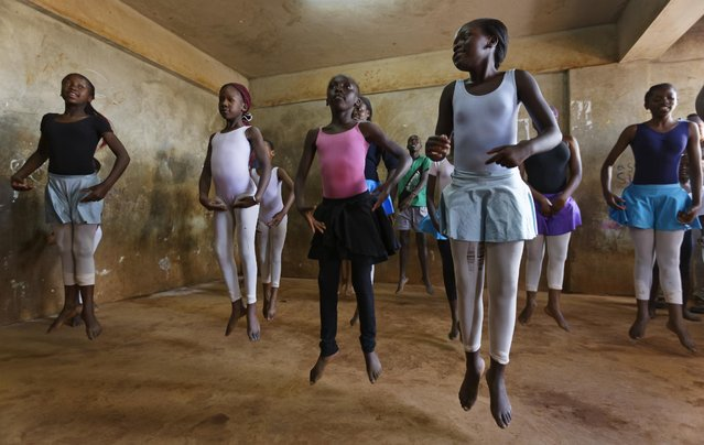 In this photo taken Friday, December 9, 2016, young ballerinas practice under the instruction of Kenyan ballet dancer Joel Kioko, 16, in a room at a school in the Kibera slum of Nairobi, Kenya. (Photo by Ben Curtis/AP Photo)