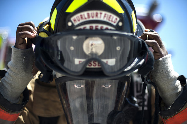 Airman 1st Class Keith Fussell, 1st Special Operations Civil Engineer Squadron firefighter, dons his helmet before training on Hurlburt Field, Fla., July 17, 2014. Firefighters spent more than an hour training on the correct ventilation techniques to maintain proper readiness to complete the mission. (Photo by Senior Airman Christopher Callaw/U.S. Air Force)