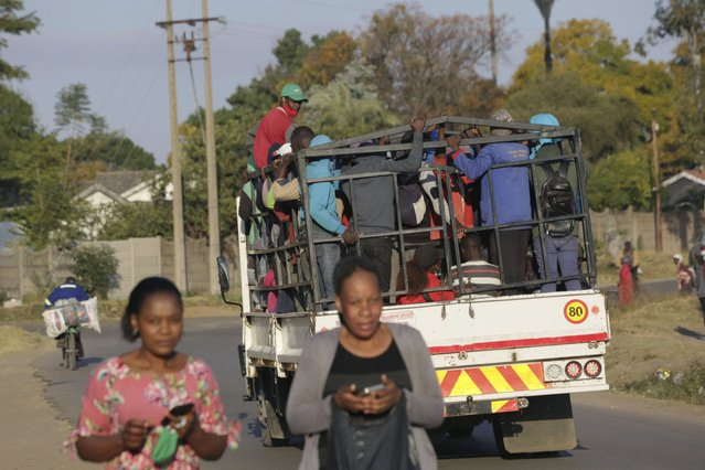 A truck loaded with people travels on a street, in Harare, Tuesday, July, 6, 2021. Zimbabwe has reactivated strict lockdown measures it once imposed when COVID-19 first hit the country last year, as the country battles a resurgence of the virus amid vaccine shortages. (Photo by Tsvangirayi Mukwazhi/AP Photo)