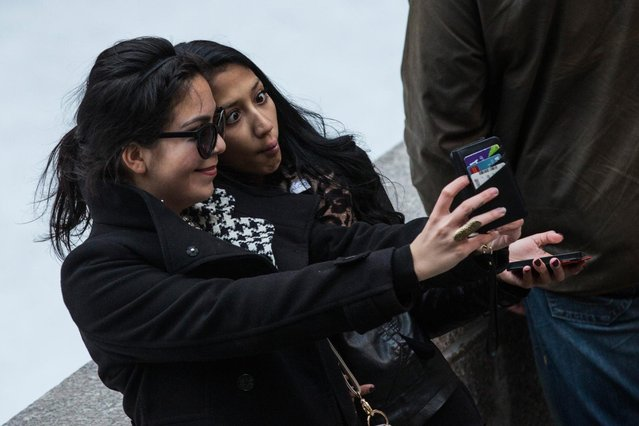 """Two women take a """"selfie"""" outside Rockefeller Center on November 19, 2013 in New York City. Oxford Dictionary named """"Selfie"""" the new word of the year. The word is defined as """"a photograph that one has taken of oneself, typically with a smartphone or webcam and uploaded to a social media website"""". The terms """"binge-watch"""" and """"twerk"""" were shortlisted. (Photo by Andrew Burton/Getty Images)"""